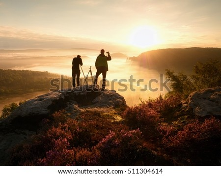Photographers stay on cliff and takes photos. Dreamy fogy landscape, orange misty sunrise in a beautiful valley below #511304614