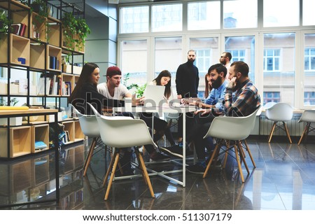 Group of casually dressed businesspeople discussing ideas in the office. Creative professionals gathered at the meeting table for discuss the important issues of the new successful startup project Royalty-Free Stock Photo #511307179