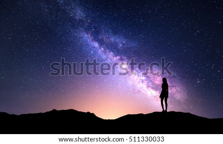Beautiful purple Milky Way with standing woman. Colorful landscape with night sky with stars and silhouette of a girl on mountain on the background of beautiful galaxy. Milky way with yellow light. #511330033