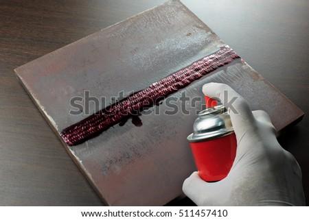 DPI or PT test weldment for finding defect (spray penetrant onto weldment)