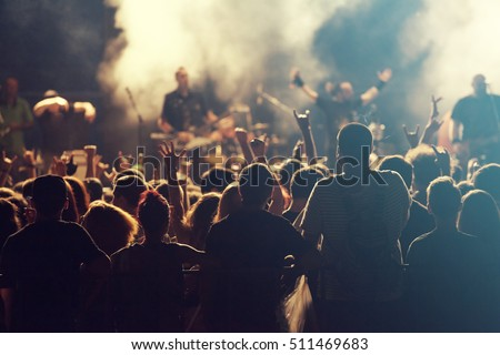 Rock concert, cheering crowd in front of bright colorful stage lights #511469683
