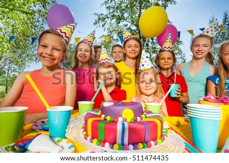 Big group of happy kids standing around B-day cake #511474435