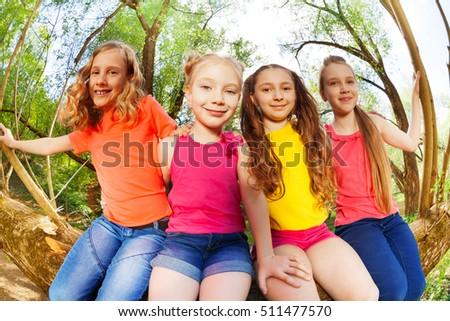 Four happy girl friends sitting on fallen tree #511477570