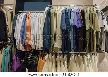 Clothing Store concept : hanging blue, white, green and orange men long sleeve shirts on hanger in clothing store for sale : beauty and fashion and business concept #511524211