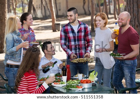Positive adults relaxing at grill party in sunny day #511551358