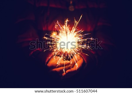 Woman holding bright festive Christmas sparkler in hand, tinted photo #511607044