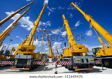 Mobile construction cranes with yellow telescopic arms and big tower cranes in sunny day with white clouds and deep blue sky on background, heavy industry  Royalty-Free Stock Photo #511649470