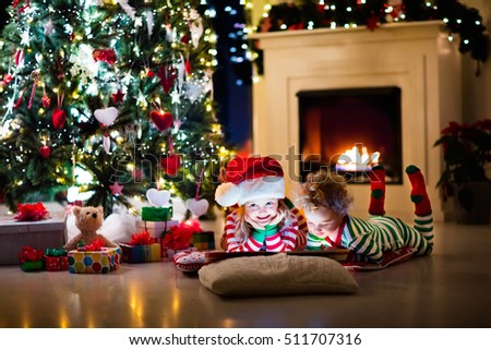 Happy little kids in matching red and green striped pajamas decorate Christmas tree in beautiful living room with traditional fire place. Children opening presents on Xmas eve. #511707316