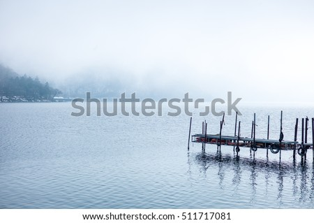 endless jetty leading over lake to the horizon with fog on morning. Abandoned jetty with nice view in natural landscape background and clear reflection from wet lake. Focus on the jetty piers #511717081