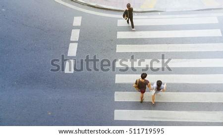 Top view of city people are walking across crosswalk in the city street.  #511719595