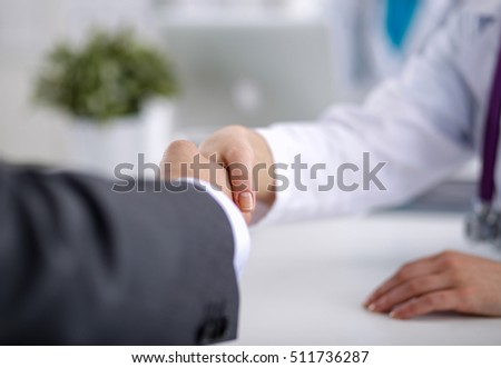 Doctor shakes hands with a patient isolated on white background #511736287