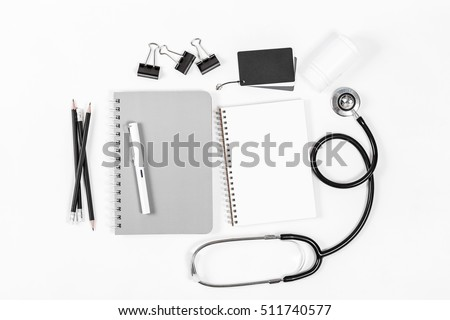 Doctor desk top view, shot from above of doctor table with notebook paper, pen, stethoscope flat lay display with copy space, top view photography project, medical doctor and healthcare concept.