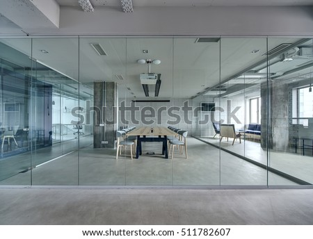Office in a loft style with white brick walls and concrete columns. There is a meeting zone with a large wooden table with gray chairs and glass partitions. Above the table there is a projector.  Royalty-Free Stock Photo #511782607