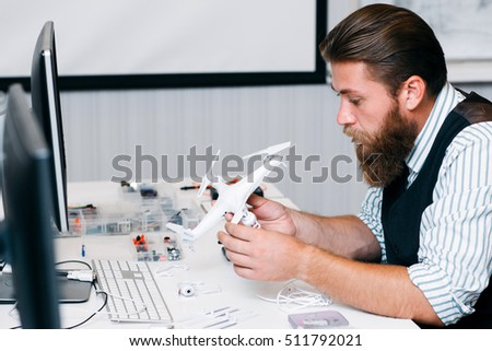 Electronic toy repair shop,. Bearded master disassembling broken hexacopter for renovation. Business, occupation, technology concept #511792021