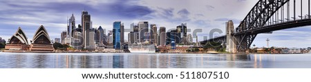 Sydney city landmarks panoramic view across Sydney Harbour along Harbour Bridge arch towards cityscape skyscrapers at sunrise Royalty-Free Stock Photo #511807510