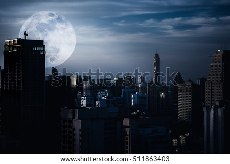 Silhouettes of skyscrapers different construction in the dark town with background of a large moon and clouds at nighttime. Dark tone and high contrast style. The moon were NOT furnished by NASA. #511863403