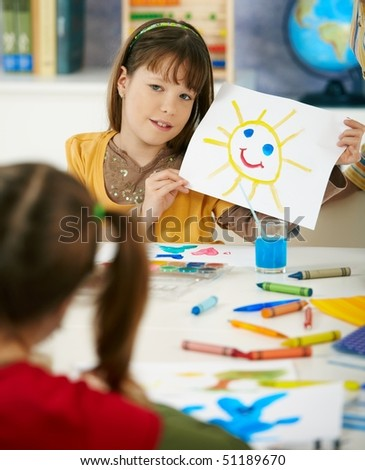 Portrait of elementary age schoolgirl showing colorful paining to classmate in art class in primary school classroom. #51189670