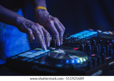 MOSCOW-1 JUNE,2016:Concert DJ play music on nightclub stage.Focus on hands of girl dj playing music&scratching tracks on midi controller.Disc jockey digital audio equipment for concerts.Female DJ #511925689