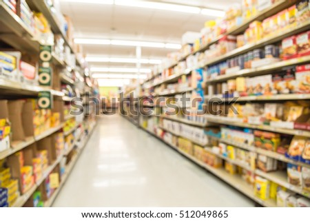 Blurred image of storage bags, cake mixes, flour, sugar, spices, oil shortening, pie filling aisle in store. Wide view supermarket shelves variety of products, defocused blur background, bokeh light. #512049865