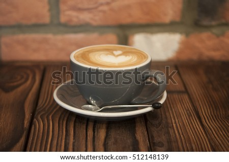 Photo of coffee in a cup, with a decorative design. Taken on wood with brick background #512148139