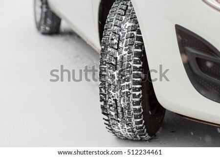 Closeup of car tires in winter. the first snow in late autumn #512234461