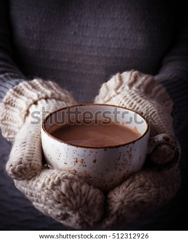 Woman in mittens holding a cup of hot chocolate.  Selective focus