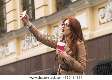Selfie time. Smart young girl in s glasses take a photo on the street with a cup of coffee. Smile and well-looking red-hair girl. Good moorning with a cofee time. #512464837