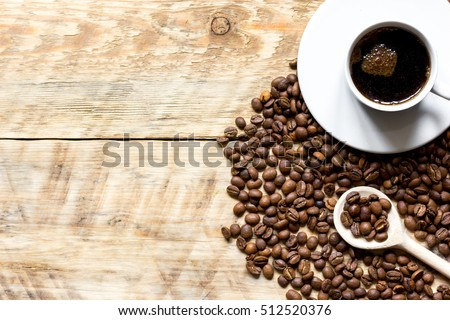 coffee beans on wooden with coffe cup table top view #512520376
