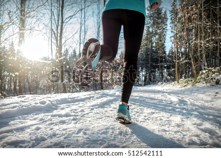 Woman Running at snowly winter under sunlight. #512542111