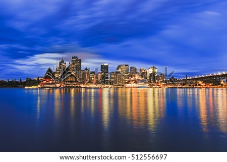 Sydney city CBD across Harbour blurred waters at sunrise when bright downtown lights reflect and blur between blue cloudy sky and flat water #512556697
