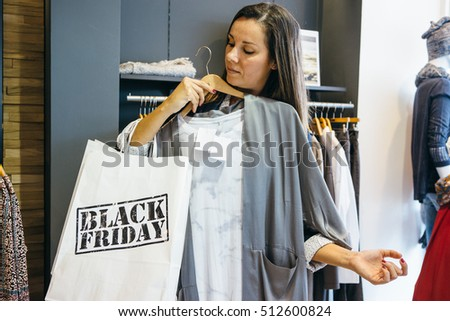 Woman with Black Friday paper bag trying new blouse while shopping. Copy space #512600824