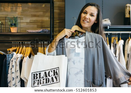 Front view of brunette woman with Black Friday bag trying blouse in store. Copy space #512601853