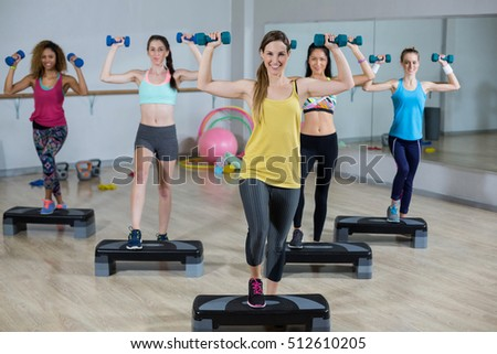 Group of women exercising on aerobic stepper in gym #512610205