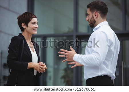 Businesspeople interacting with each other in office premises #512670061
