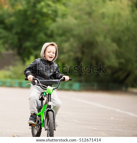portrait of adorable little urban boy wearing black leather jacket. City style. Urban kids. The boy learns to ride a bike. Child driving a bicycle. #512671414