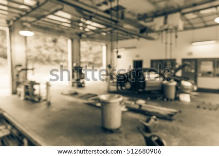 Blurred image of car in auto shop. Defocused background of modern repair shop. Small car oil change service station at Little Rock, Arkansas, US. Repair shop with working auto mechanic. Vintage filter #512680906