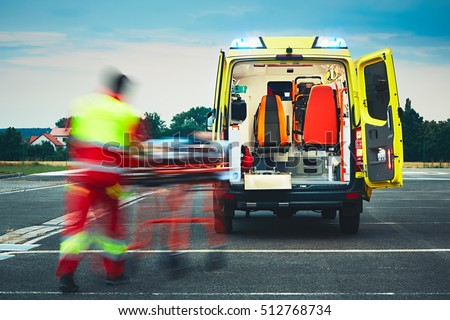 Emergency medical service. Paramedic is pulling stretcher with patient to the ambulance car. Royalty-Free Stock Photo #512768734