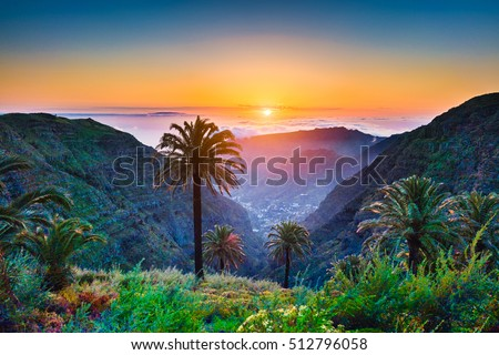 Beautiful view of amazing tropical scenery with exotic palm trees and mountain valleys above wide open sea in golden evening light at sunset with blue sky and clouds in summer, Canary Islands, Spain Royalty-Free Stock Photo #512796058