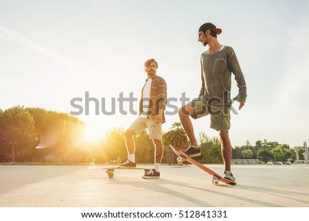 Young people training with longboard with back sun light- Skaters friends outdoor in urban city with skateboards  -Extreme sport and friendship concept - Focus on right man's feet - Warm filter #512841331
