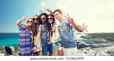 summer holidays, vacation, travel, technology and people concept - smiling young hippie friends taking picture by smartphone on selfie stick and showing peace gesture over beach background #512862499