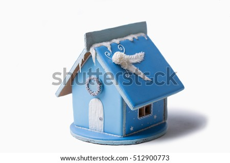 Gingerbread house. Christmas pastries. Gingerbread in the snow. In the background a blue sky with copy space.