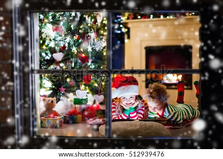 Happy little kids in matching red and green striped pajamas decorate Christmas tree in beautiful living room with traditional fire place. Children opening presents on Xmas eve. #512939476