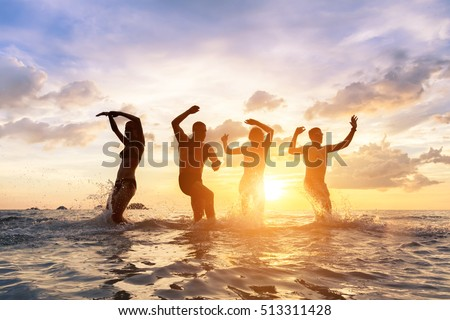 Group of young people having fun dancing in the sea with splashes of water, cheerful happy friends #513311428