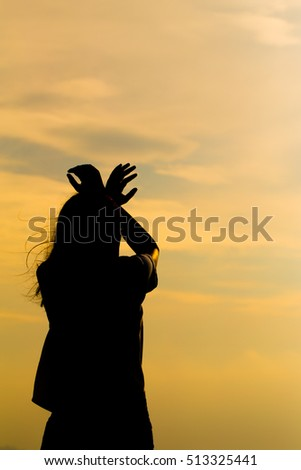 Silhouette of young woman standing at relax pose or freedom pose or chill pose on the beach during sunset. #513325441