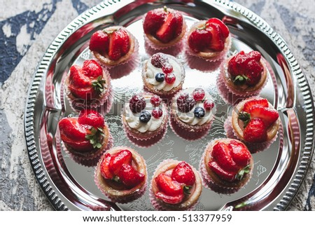 Delicious cupcakes with fresh strawberries, raspberries and blueberries #513377959