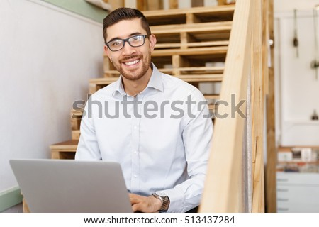 Portrait of young man sitting at the stairs in office #513437284