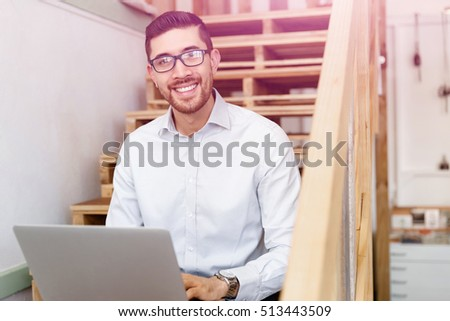 Portrait of young man sitting at the stairs in office #513443509