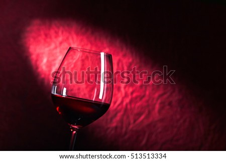 glass of red wine on a dark red background #513513334