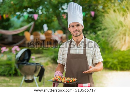 Handsome man preparing barbecue for friends, France #513565717