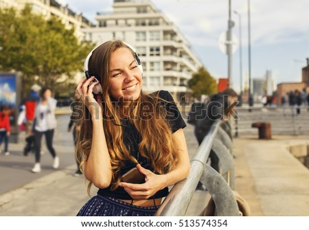 Beautiful blonde girl with headphones and mobile listening to the music in the city #513574354
